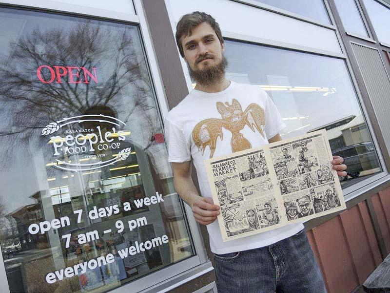 Simon Borst at People's Food Co-op holding an issue of the People's Food Co-op Coop Scoop with a two-page spread of his comic storytelling.