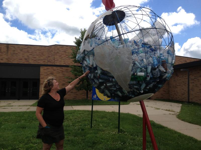 Sabine LeDieu stands next to her sculpture she made with the help of students from Harper Creek Middle School.