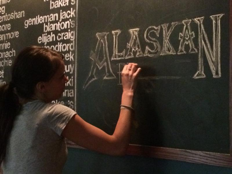 Alyssa Prince works on creating chalk art for Central City Tap House's downtown location.