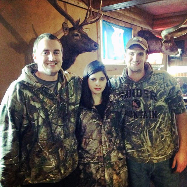 Liana Satenstein of Vogue.com stands beside two Michigan duck hunters at Louie's Trophy House Grill in Kalamazoo