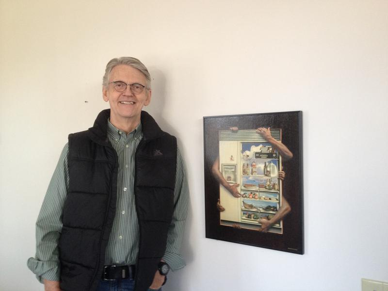 "Doug Dykehouse next to a print of his painting ""Adore to Access"""
