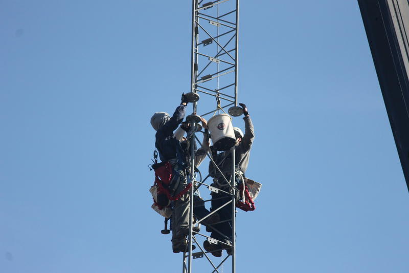 Newkirk Electric workers on a cell tower