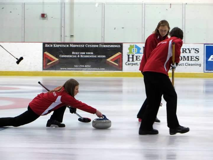 Stephanie Senneker slides the stone at the USA Arena Curling National Championships. Pam Nelson is sweeping in front. Nicole Brinkmann is sweeping in back.