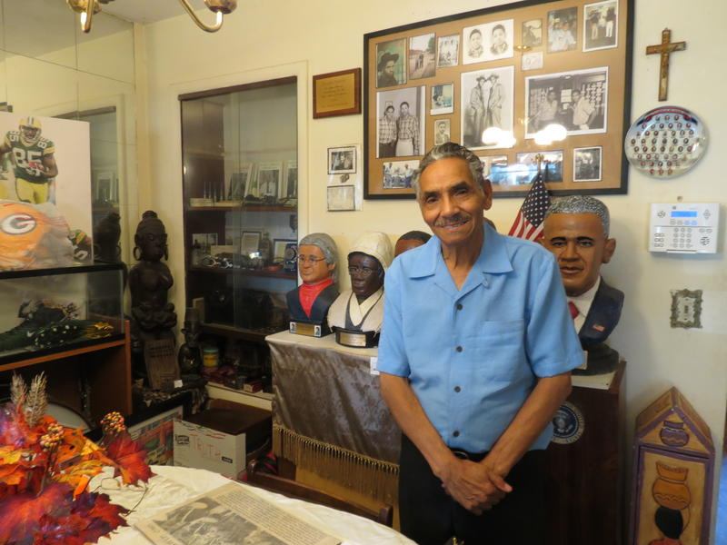 Murphy Darden stands in his house surrounded by African American artifacts he's collected and his historical art works