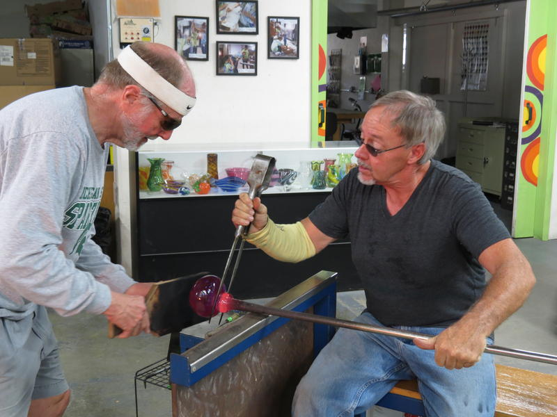 Allen Buhl (left) helps to flatten out the bottom of a glass pumpkin that Philip Dawson (right) is making at Glass Art Kalamazoo in 2015.