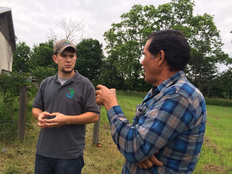Farmer Arturo Pendoja talking with Kyle Mead, ground water technician with the Van Buren Conservation District
