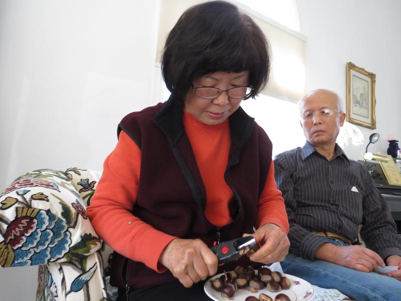 Jei Yoo (right) watches as his wife Jenny Yoo (left) peels chestnuts at their home in Kalamazoo