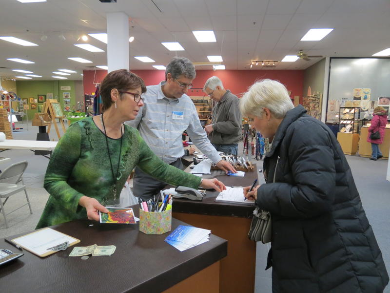 Gloria Badiner (left) and David Smallcombe help customer Lisa Huff check out at the counter at the Signature Artist Gallery. The gallery is only open during the month of December.