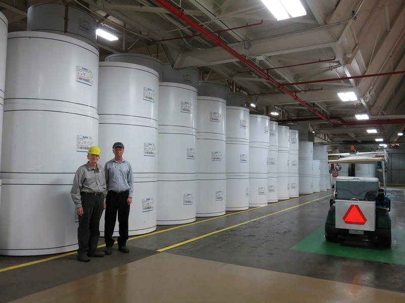 Cody and GPI's Mike Farrell stand by stacked rolls of paper. Each roll weighs about 2.5 tons, or as much as a minivan.