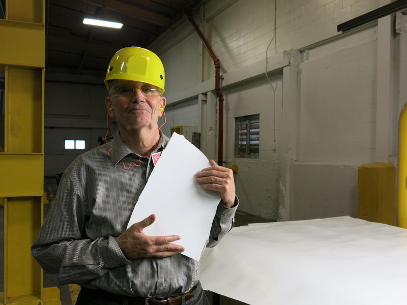 Frank Cody holds a piece of paper at Graphic Packaging International's plant on Pitcher Street in Kalamazoo