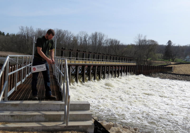Mark Mills with the Michigan Department of Natural Resources closes the gate to the temporary water control structure upstream of the Otsego Township Dam. The structure is there to help take pressure off of the dam while the cleanup takes place.