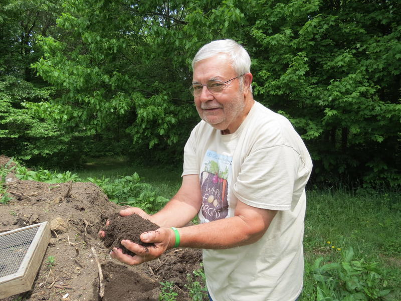 Retired MSU microbial ecologist Mike Klug scoops up a hand full of soil from his compost.