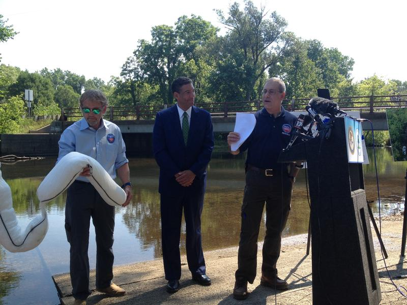 An EPA employee holds one of the types of booms used to clean up the Kalamazoo River oil spill in 2010. Patrick Miles of the U.S. Attorney's Office (middle) and acting EPA regional administrator Robert Kaplan (right) made the announcement about the Enbrid