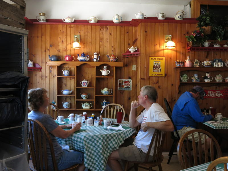 Joan and Roy Miller sit by a wall of teapots inside the restaurant