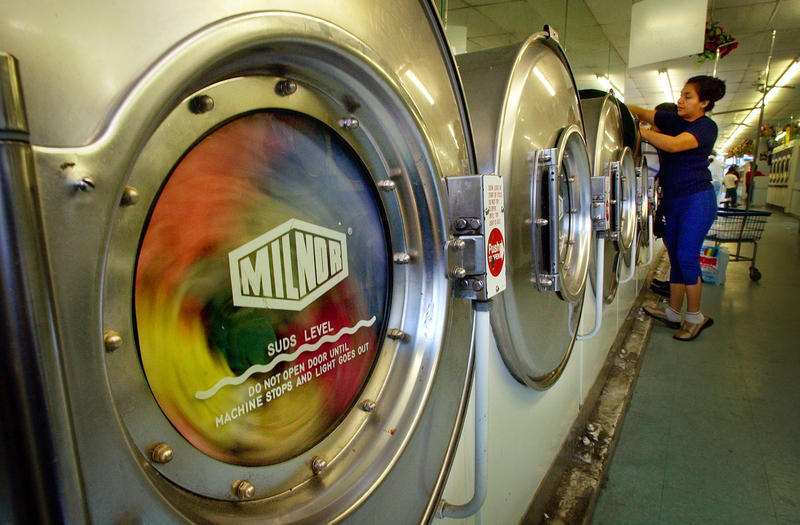 An unidentified woman loads clothes into a washing machine at a coin-operated laundry in Los Angeles' Echo Park district, Wednesday, Dec. 10, 2003. A freeze on regulations Gov. Arnold Schwarzenegger declared on his first day in office may delay or alter a