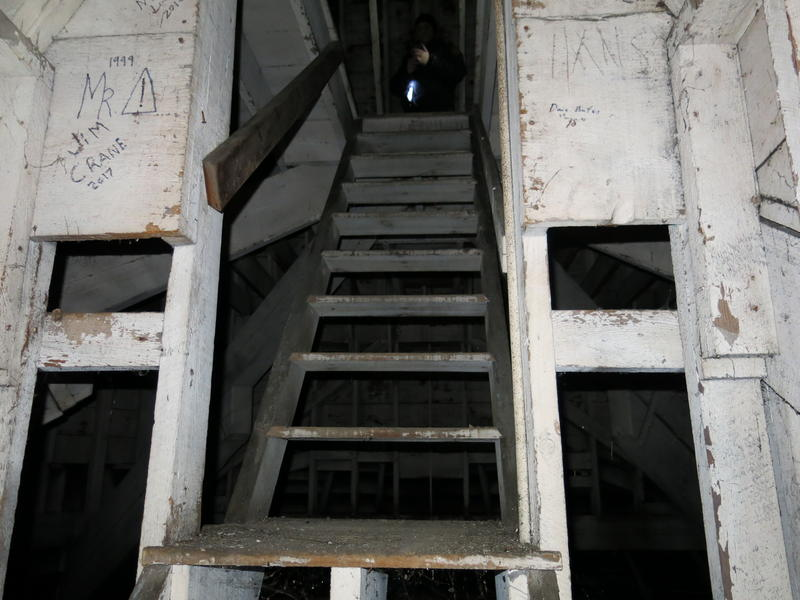 The wooden staircase over the empty tank that leads to a platform under the roof