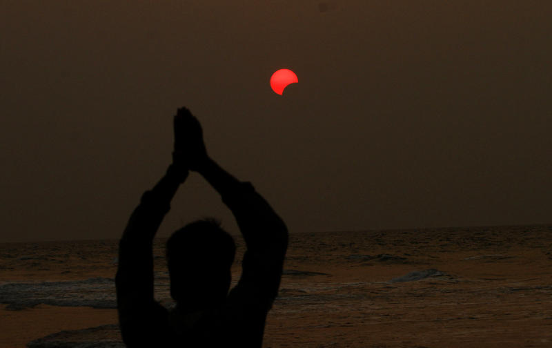 An Indian fisherman prays to a partial solar eclipse seen in the sky over Bay of Bengal in Konark, 60 kilometers (37 miles) from eastern Indian city Bhubaneswar, India, Wednesday, March 9, 2016.