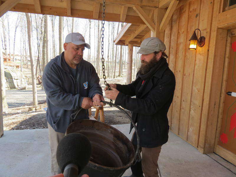 Ryan Sprague (left) and Kevin Finney (right) remove a pot used for boiling maple syrup. The syrup will be featured at the Intertribal Food Summit.