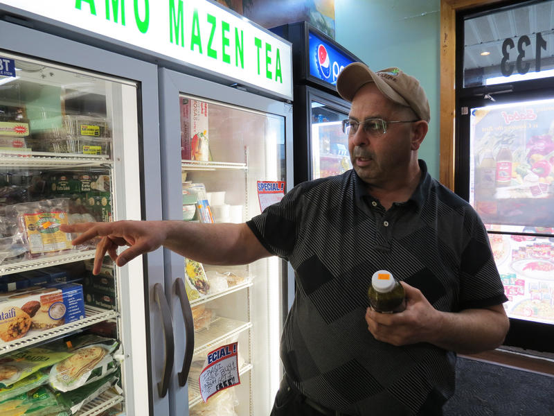 Owner of Bab El Salam in Portage, Mazen, points at pre-packaged, halal meat he sells at his store.