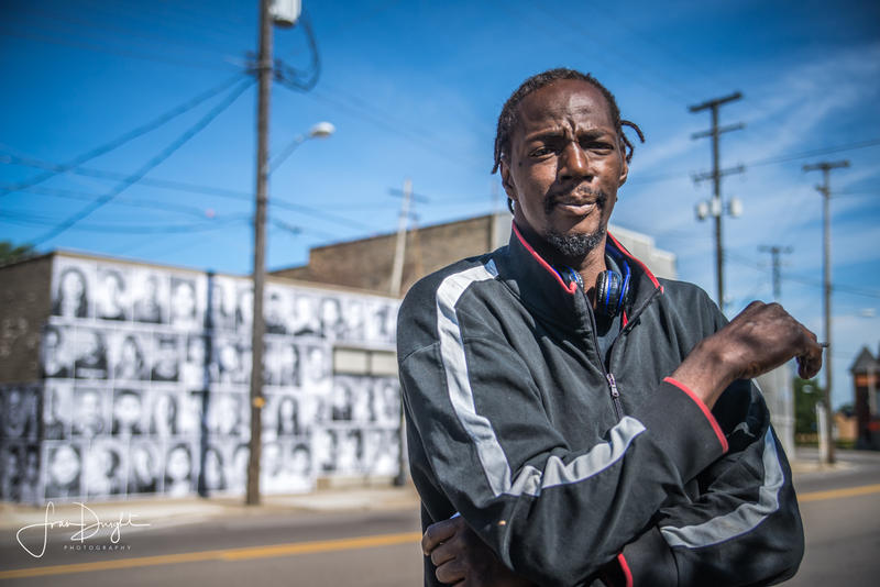 "William Pitts stands across the street from the photo art project ""We Are Edison."" His portrait is on the old Color Lab building along with many of his neighbors."