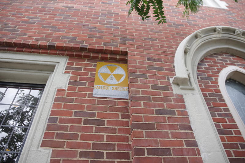 "The faded ""fallout shelter"" sign on the side of the church."