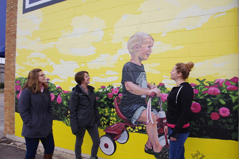 The artists of the South Haven Area Mural Project (Sh-amp) stand in front of their first completed mural at Rock 'N' Road Cycle. From left to right: Kayla Wyszynski-Ridley, Sam Dustin, and Kelly Gleeson.