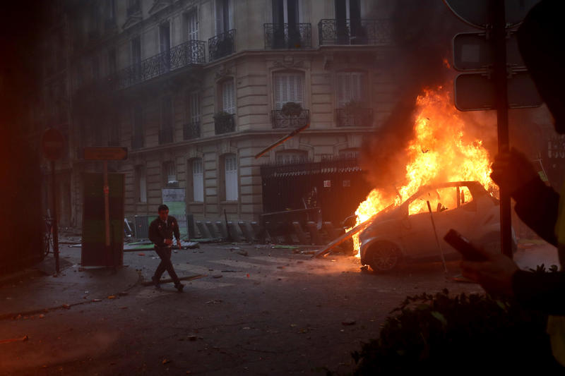 A demonstrator runs past a burning car during a demonstration in Paris on Saturday, Dec. 1, 2018, against an increase in fuel taxes.  (AP Photo/Thibault Camus)