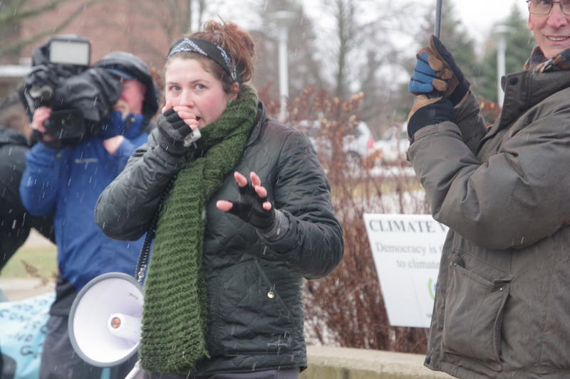 A young woman speaks through a loudspeaker as rain falls at the Kalamazoo Global Climate Strike rally on Friday.
