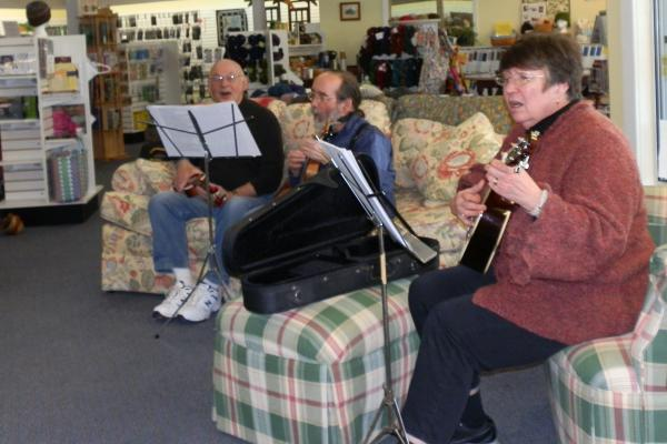 Members of the Battle Creek Ukulele Group jam together at Your Local Yarn Shop in Battle Creek.