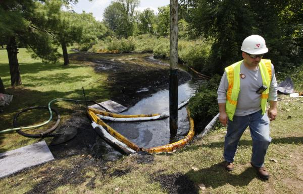 Worker monitors oil removal from Talmadge Creek in July 2010