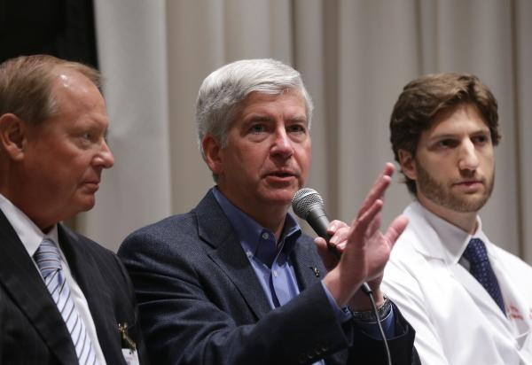 Gov. Rick Snyder, center, joins Detroit hospital officials on July 1, 2013, to discuss the Healthy Michigan plan.