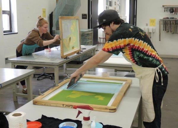 Students Leah Rutt and Nick Errard screen printing at the Gwen Frostic School of Art at Western Michigan University.