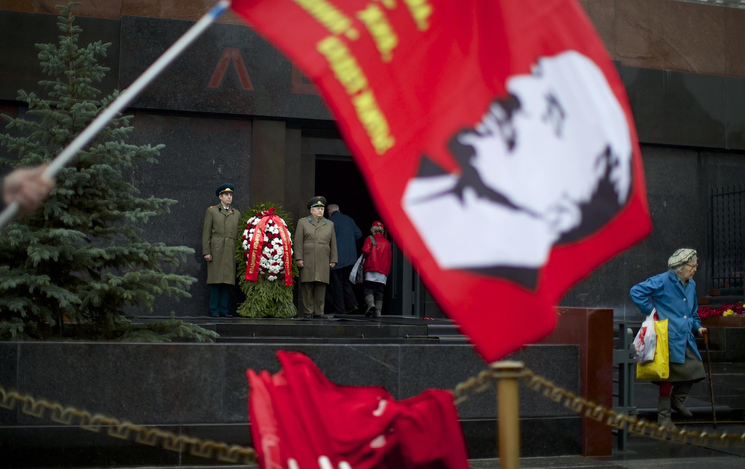 between the lines worshipping at lenin s tomb  a communist supporter holds a red flag a portrait of soviet founder vladimir lenin at moscow s red square russia wednesday nov