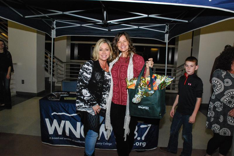 Two women posing in front of WNCW tent with gift bag