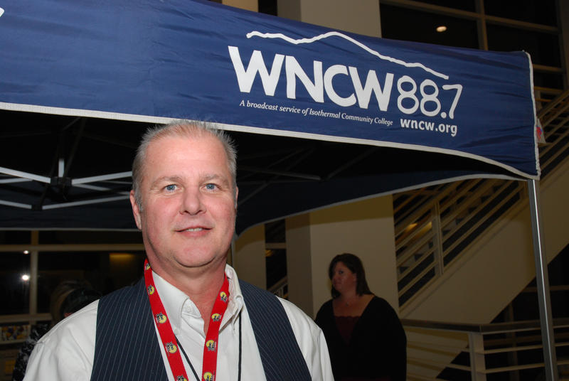 Radio host with tent logo in background