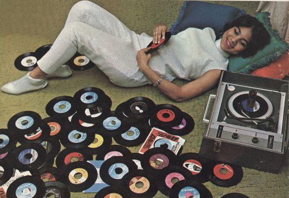 woman on floor with record player and 45 records