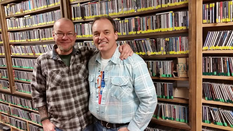 Scotty Robertson and Joe Kendrick standing in front of WNCW's Music Library