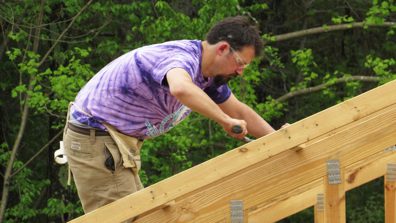 Man on roof volunteering for Habitat for Humanity