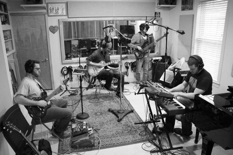 Black and white image of band members playing music in studio