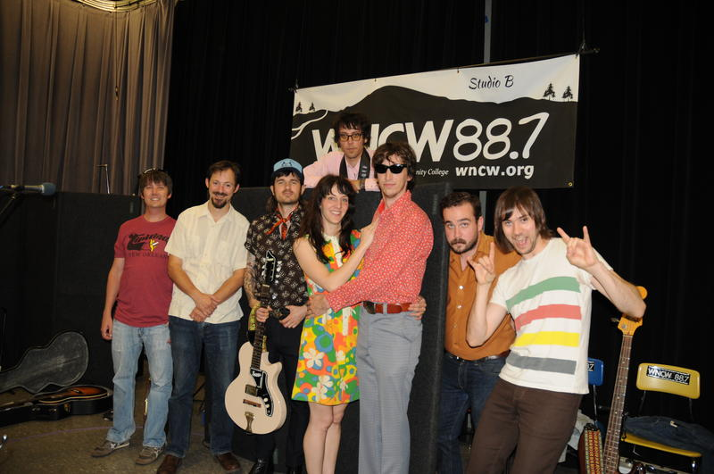 Image of Daniel Romano Band Members hanging out joking underneath WNCW banner with DJ Martin Anderson