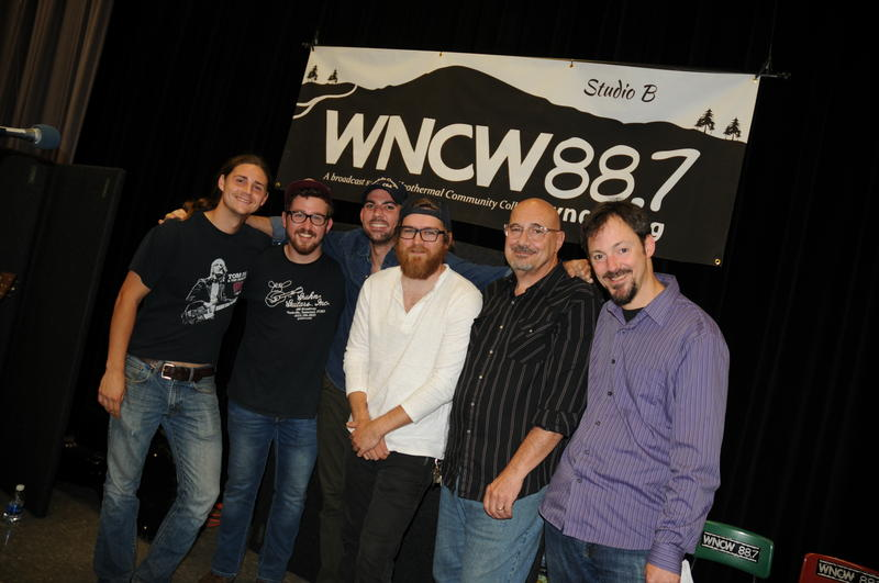 Band members with WNCW DJ with station banner in the background