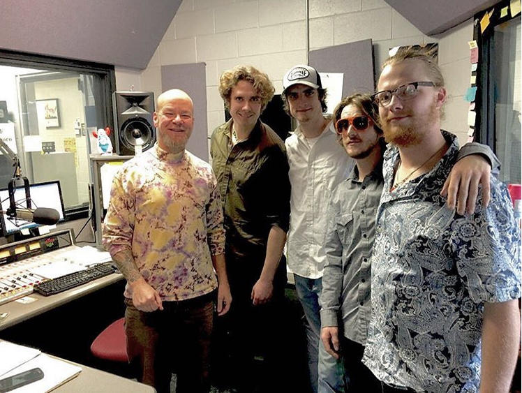Image of band members in radio station control room with DJ