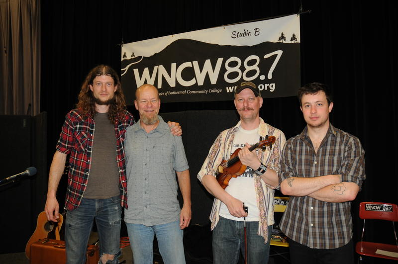 Image of band members smiling and posing in Studio B with DJ Scotty Robertson