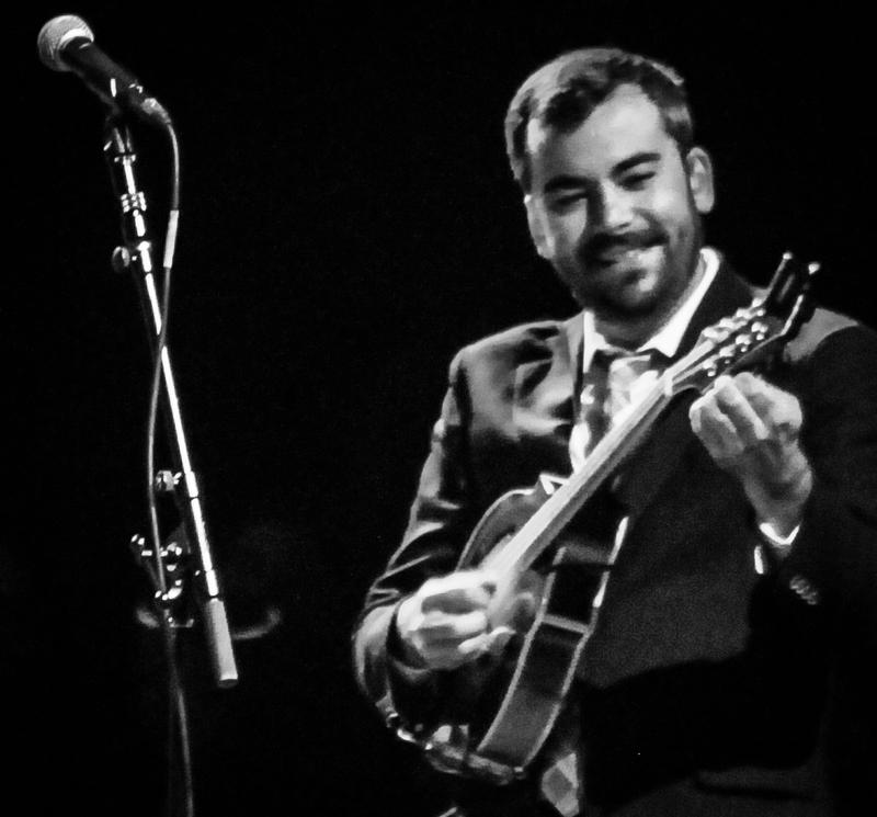 Image of Mike Guggino smiling playing mandolin