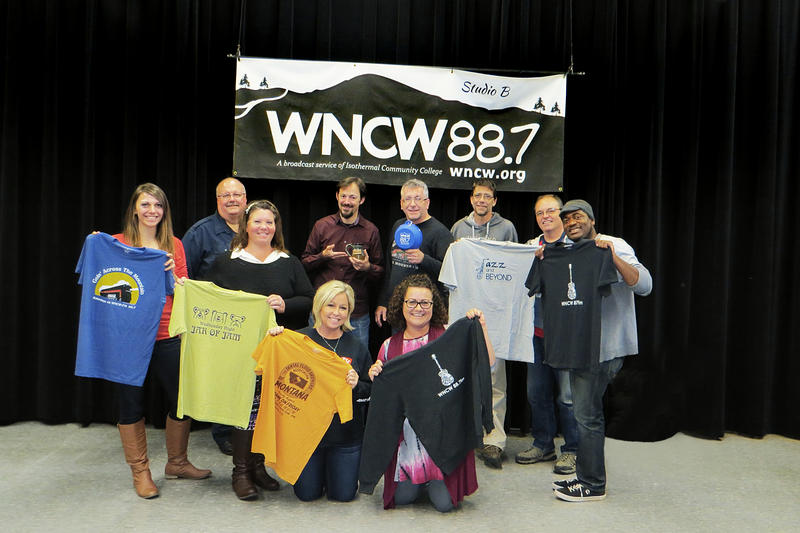 WNCW Staff stand in Studio B to show the new thank you gifts available during the fall fund drive season.