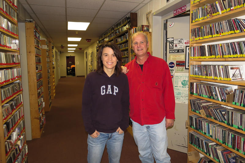 Image of female and male smiling, standing in front of cds at radio station