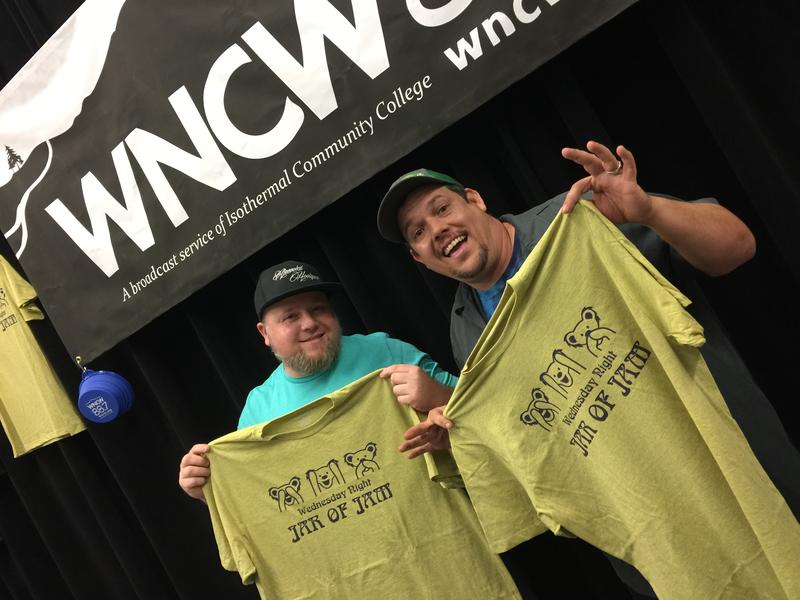 Two men holding wncw t-shirts