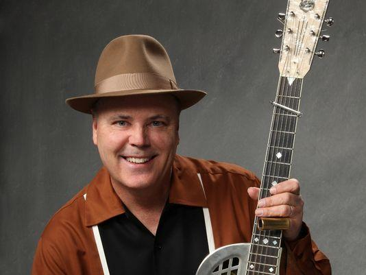 musician smiling wearing hat holding instrument