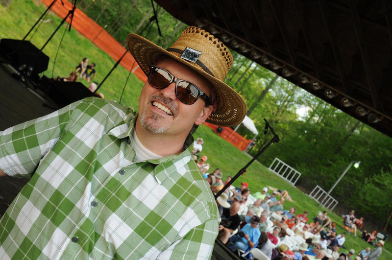 Man wearing hat and sunglasses smiling and having fun at festival