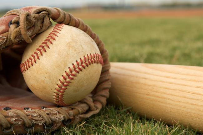 Baseball in glove laying in grass beside a baseball bat.